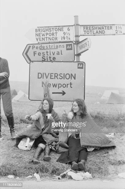Two female festival goers and music fans sit underneath a signpost as they try to thumb a lift home after attending the Isle of Wight Festival 1970...