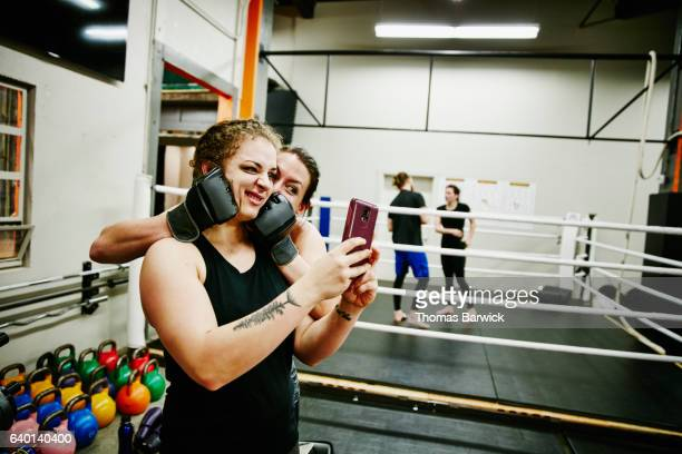 two female fighters taking self portrait with smartphone after training session in gym - boxen sport stock-fotos und bilder