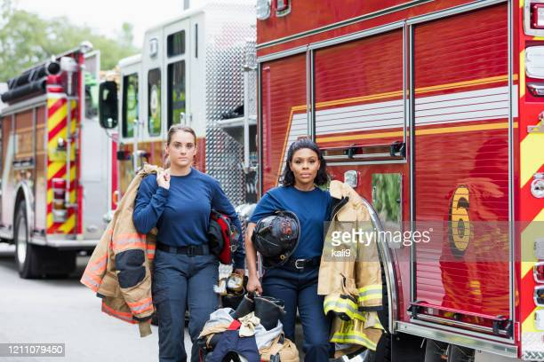 two female firefighters walking next to fire trucks - firefighter stock pictures, royalty-free photos & images