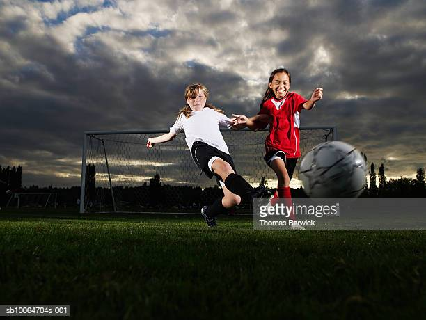 two female football players (10-11) running after ball on pitch - tacler photos et images de collection