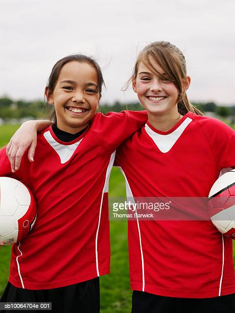 Two female football players (10-13) standing in pitch, arms around, holding balls