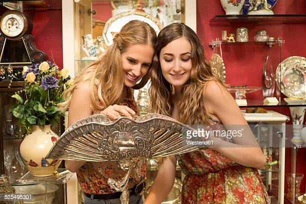 Two female friends admiring Art Deco bowl in an antique shop