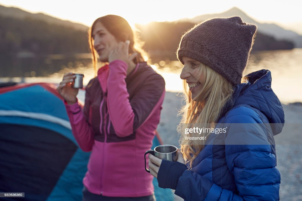 Two female friends at tent holding mugs : Stock-Foto