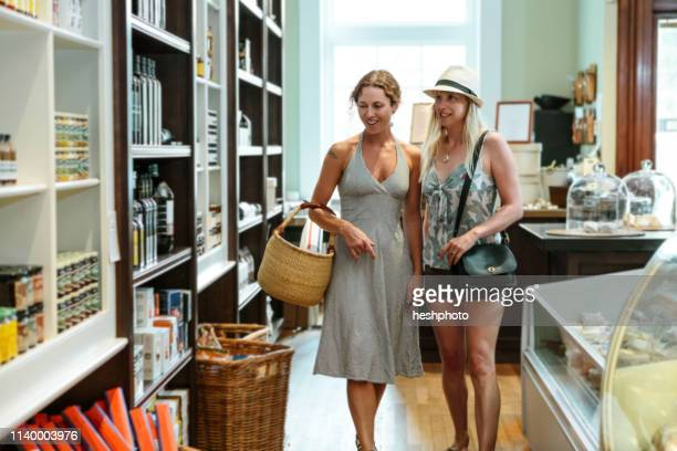 two female friends browsing in organic grocery - heshphoto fotografías e imágenes de stock