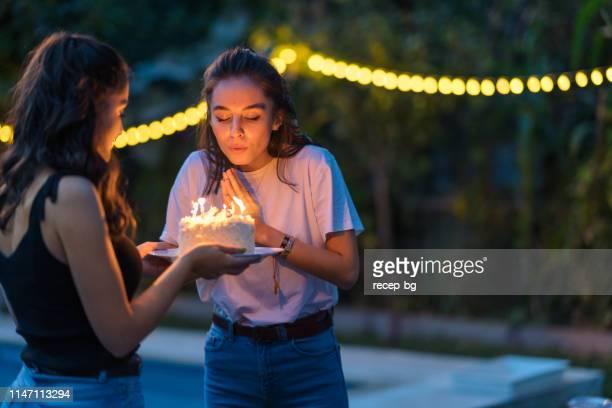due amiche che festeggiano la festa di compleanno - soffiare foto e immagini stock
