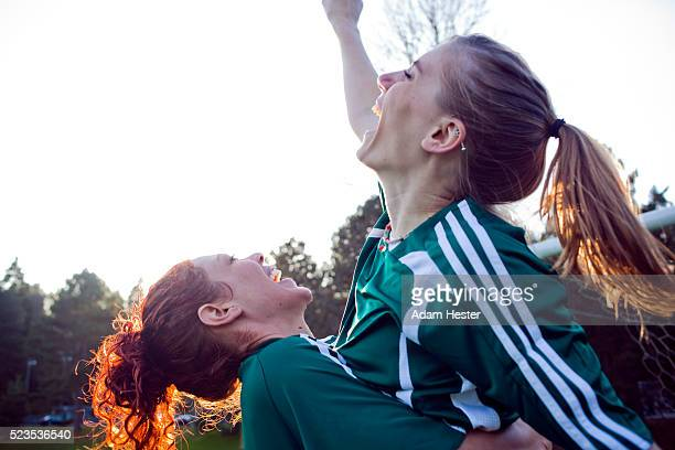 two female friends cheering - sportmannschaft stock-fotos und bilder