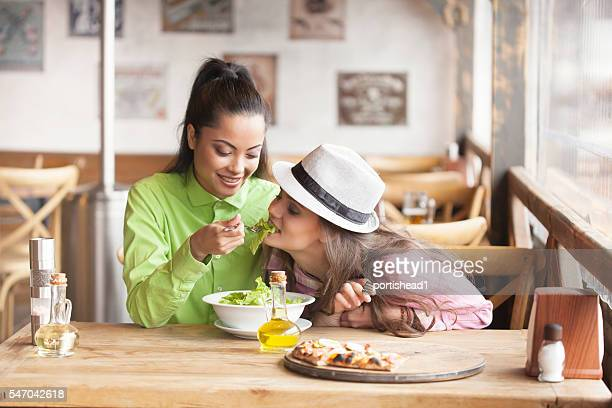 Two female friends dinig together at restaurant