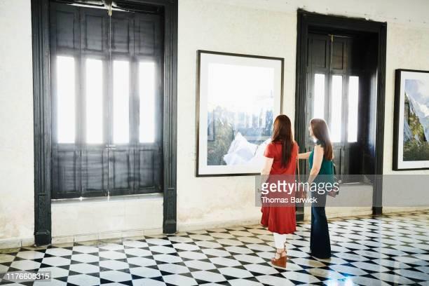 two female friends discussing details of artwork while shopping in art gallery - ausstellung stock-fotos und bilder