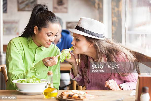 Two female friends eating salad and pizza at restaurant