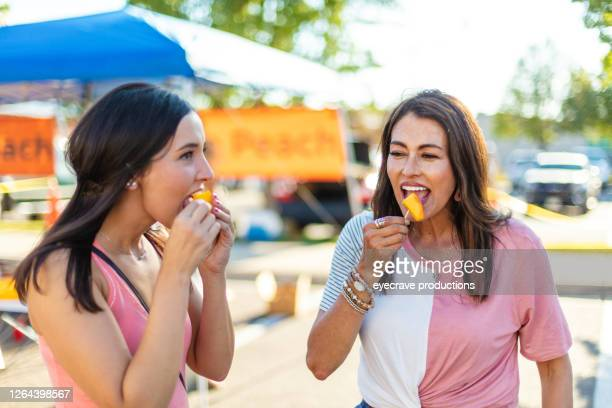 two female friends enjoying a farmer's market together - eyecrave  stock pictures, royalty-free photos & images
