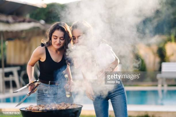 two female friends enjoying bbq party - bbq stock pictures, royalty-free photos & images