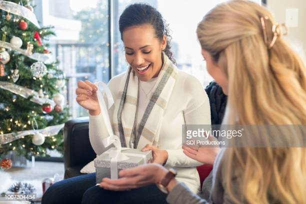 two female friends exchange christmas gifts on couch - receiving stock pictures, royalty-free photos & images