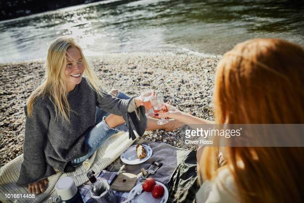Two female friends having a picnic at the riverbank