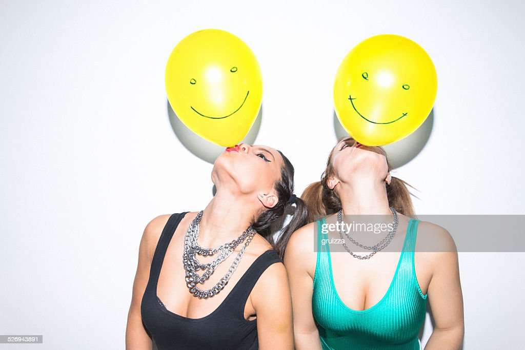 Two female friends having fun blowing up balloons on party : Stock Photo