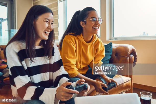two female friends having fun playing video games