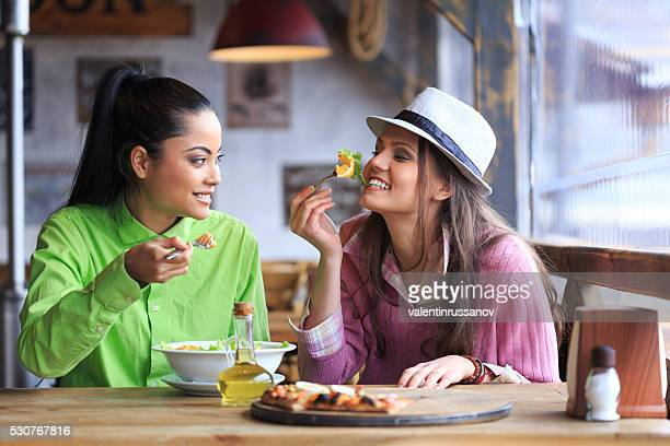 Two female friends having lunch in restaurant