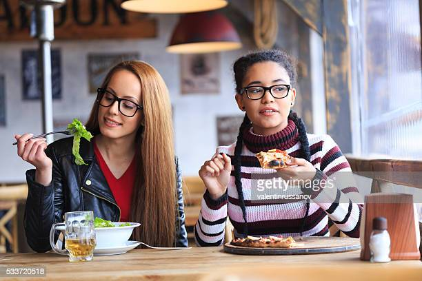 Zwei weibliche Freunde haben Mittagessen im Restaurant