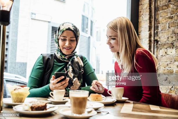 Two female friends in cafe looking at phone and smiling