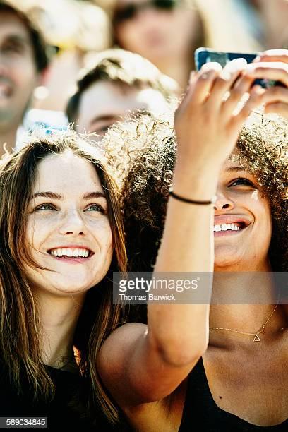 Two female friends in crowd taking selfie