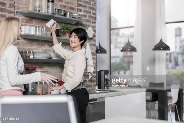 Two female friends in modern kitchen with city view