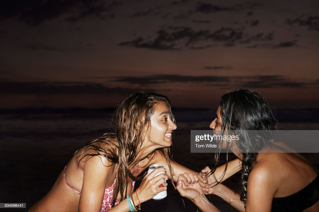 Two female friends laugh together on beach