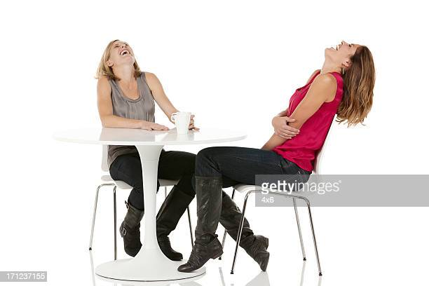 Two female friends laughing at coffee table