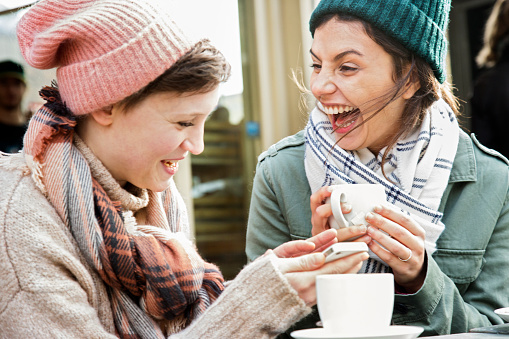 Two female friends laughing, drinking tea, in outside urban foodmarket cafe, in autumn time. - gettyimageskorea