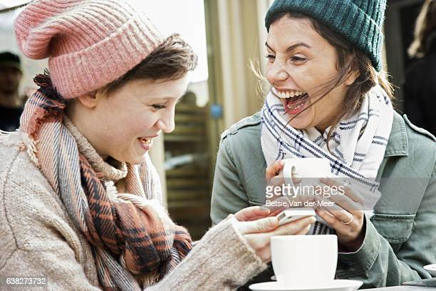 Two female friends laughing, drinking tea, in outside urban foodmarket cafe, in autumn time.
