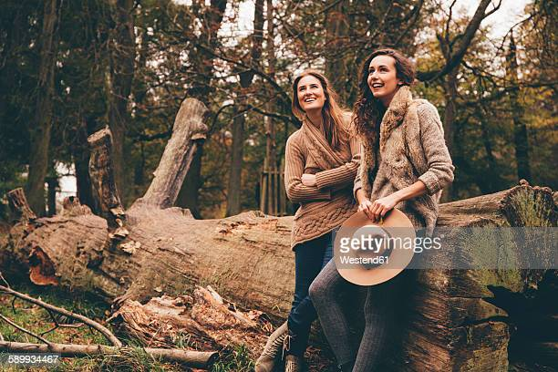 Two female friends leaning on tree trunk in an autumnal park
