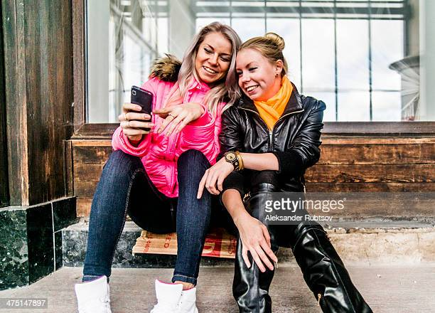 Two female friends looking at mobile phone