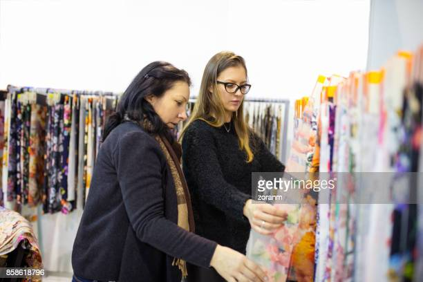 two female friends looking fabric sample - next to stock pictures, royalty-free photos & images