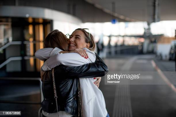 two female friends, meeting at the airport - embracing stock pictures, royalty-free photos & images