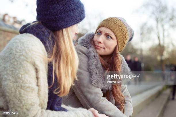 Two female friends outdoors, sitting on steps, fooling around, pulling faces