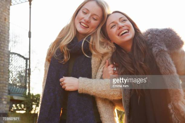 Two female friends outdoors, walking arm in arm, laughing