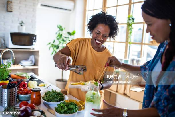two female friends preparing lemonade in the kitchen - vegetarianism stock pictures, royalty-free photos & images