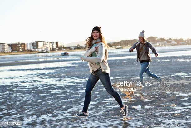 two female friends running with dog on the beach - warm clothing stock pictures, royalty-free photos & images