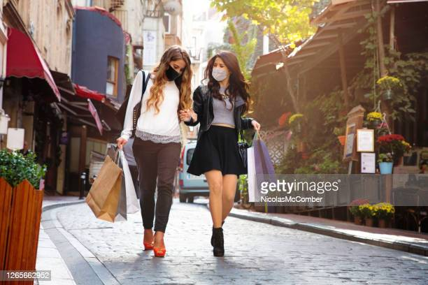 two female friends shopping outdoors in istanbul, masks on - female friendship stock pictures, royalty-free photos & images