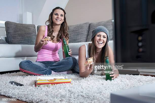 Two female friends side by side on carpet at home watching television