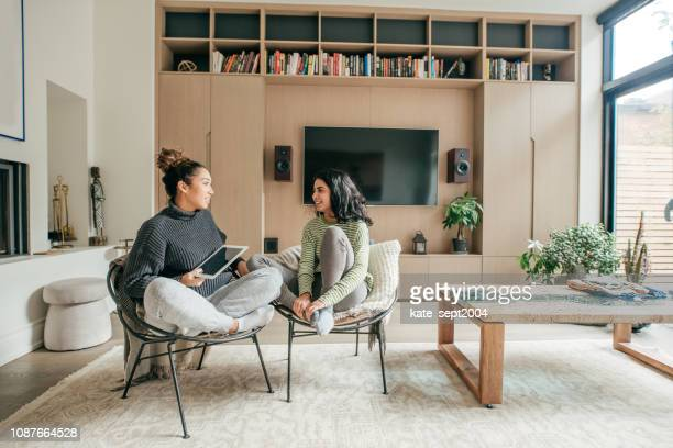 two female friends sitting in a living room - roommate stock pictures, royalty-free photos & images