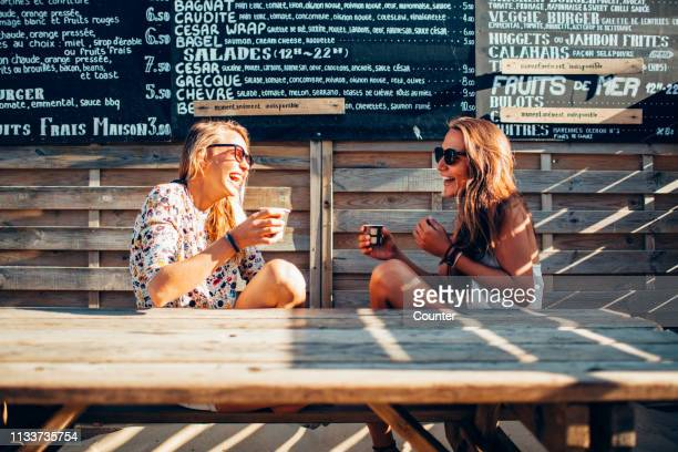 two female friends sitting laughing, drinking in beach bar - french cafe stock photos and pictures