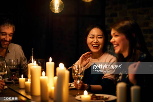 two female friends sitting next to each other and laughing during meal - dinner party stock pictures, royalty-free photos & images