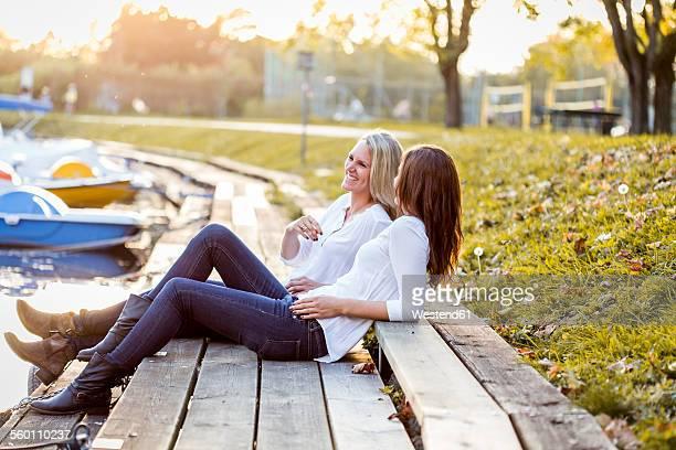 Two female friends sitting on boardwalk