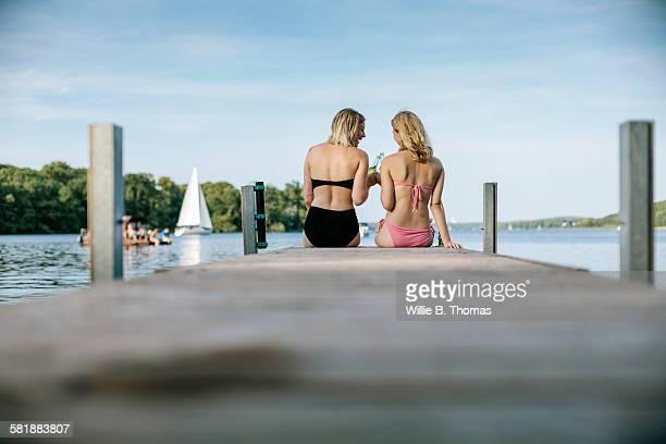 Two female friends sitting on pier