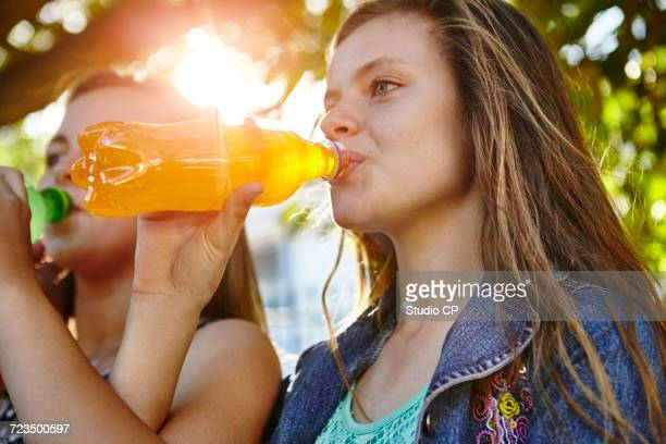 Two female friends sitting outdoors, drinking soft drinks