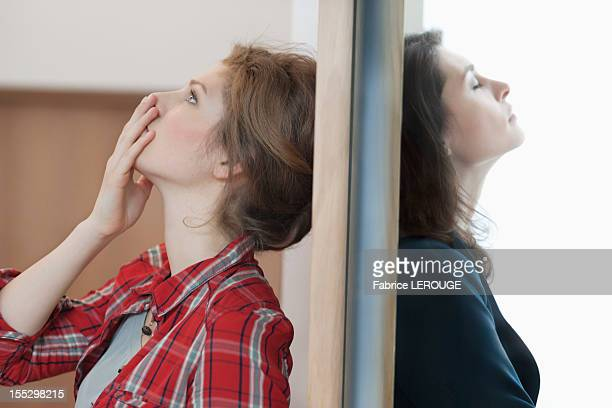 Two female friends standing back to back against a door