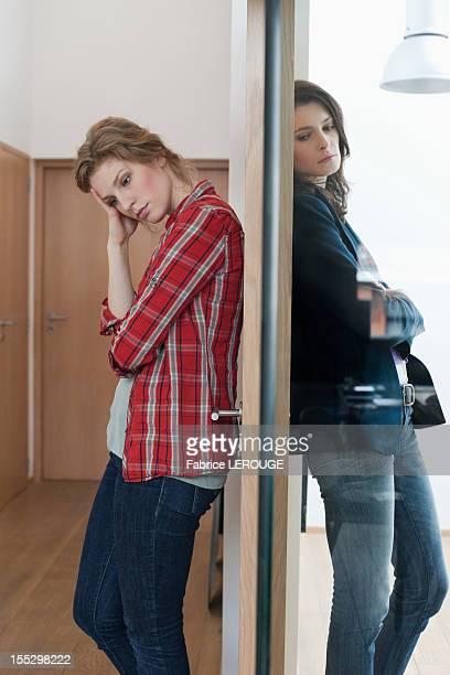 two female friends standing back to back against a door - relatieproblemen stockfoto's en -beelden
