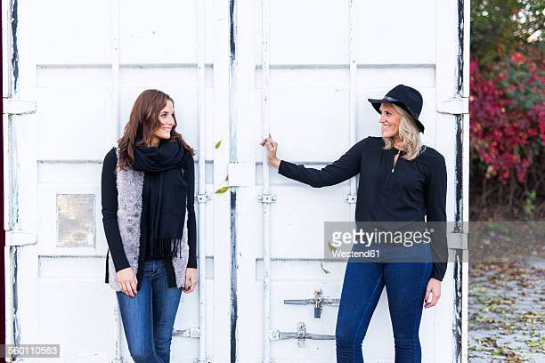 two female friends standing in front of a container - seitenblick stock-fotos und bilder