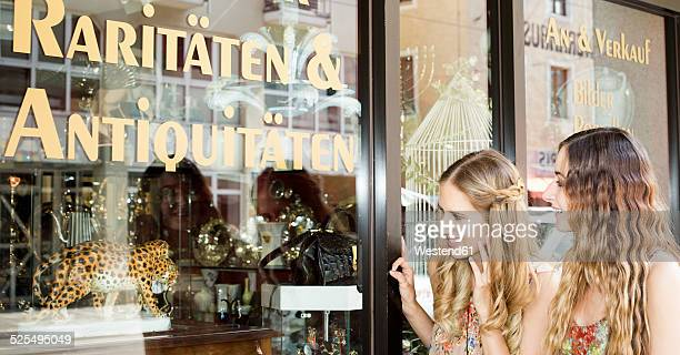 Two female friends standing in front of the window of an antique shop