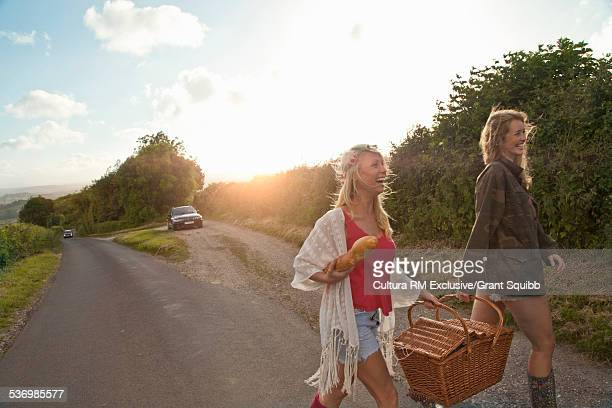 Two female friends strolling on rural road with picnic basket