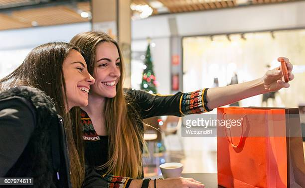 Two female friends taking a selfie at shopping center